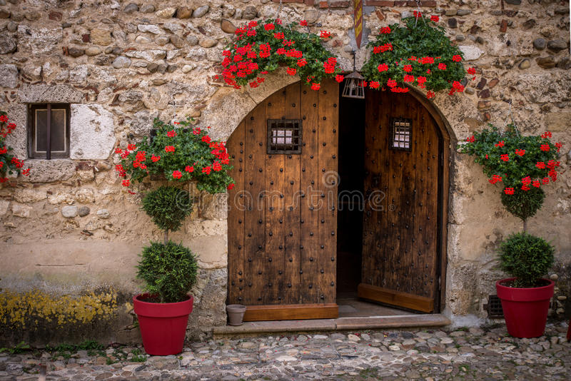 Typical facade of the old Provencal stone house Perouges, France. Typical facade of the old Provencal stone house with wooden doors decorated with colorful royalty free stock images