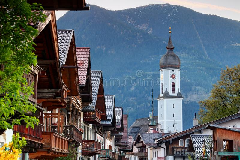 Typical German houses and church in Garmisch with Wank mountain royalty free stock photography