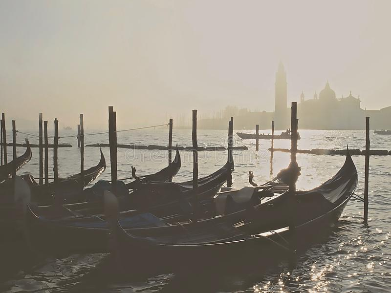 Typical gondolas in Venice with fog. Gondolas in venice during fog in the morning sun royalty free stock photos
