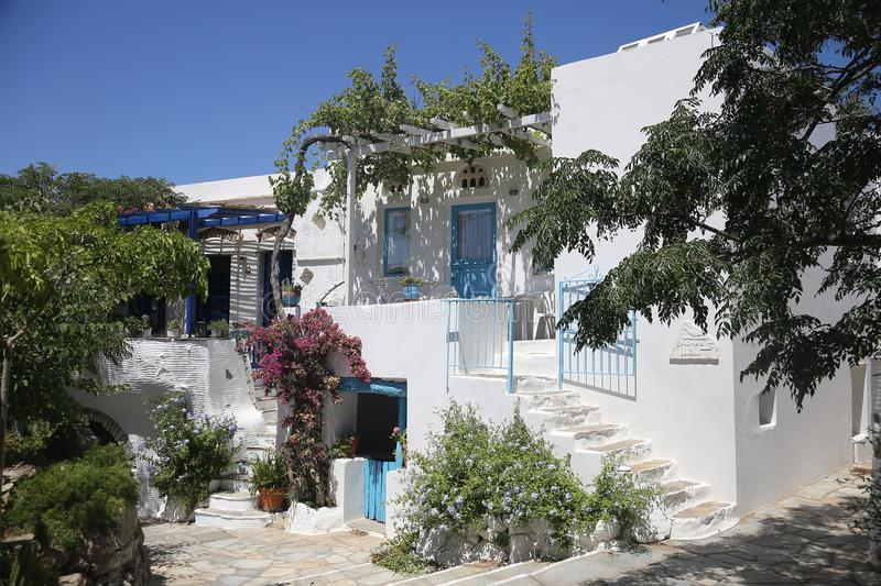 Typical greek island whitewashed house in Tinos, Greece. A traditional greek island whitewashed home surrounded by vegetation. Town of Pyrgos, Tinos Island stock images