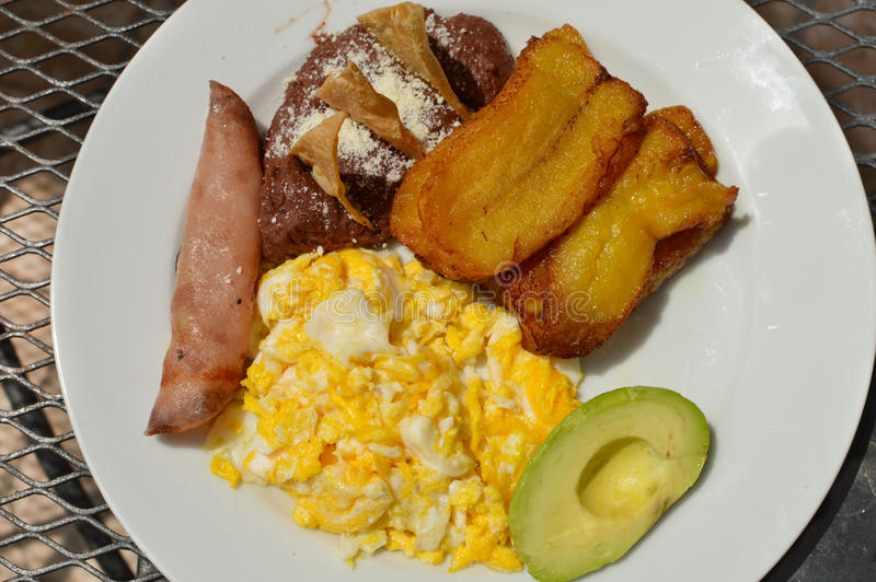 Typical Honduran breakfast of scrambled eggs, fried plantain, avocado, refried beans, tortilla chips and ham stock images