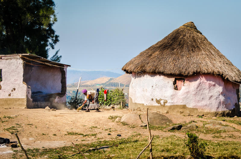 Typical house. African woman cleaning garden. South Africa. Typical rural house. Woman cleaning garden. Zululand rural houses apartheid, bantustan KwaZulu Natal stock images