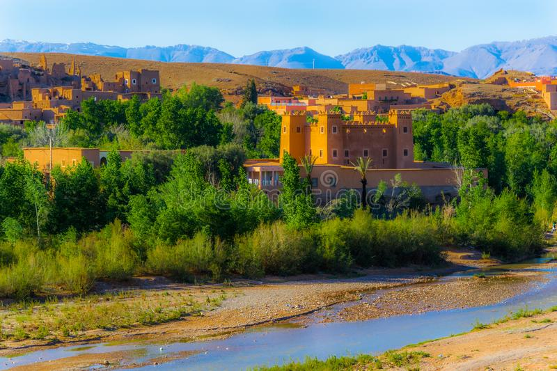 Typical house made of clay in Morocco. Typical house made of clay, in the middle of an oasis, in front of a river and some higher mountains in the background stock photos