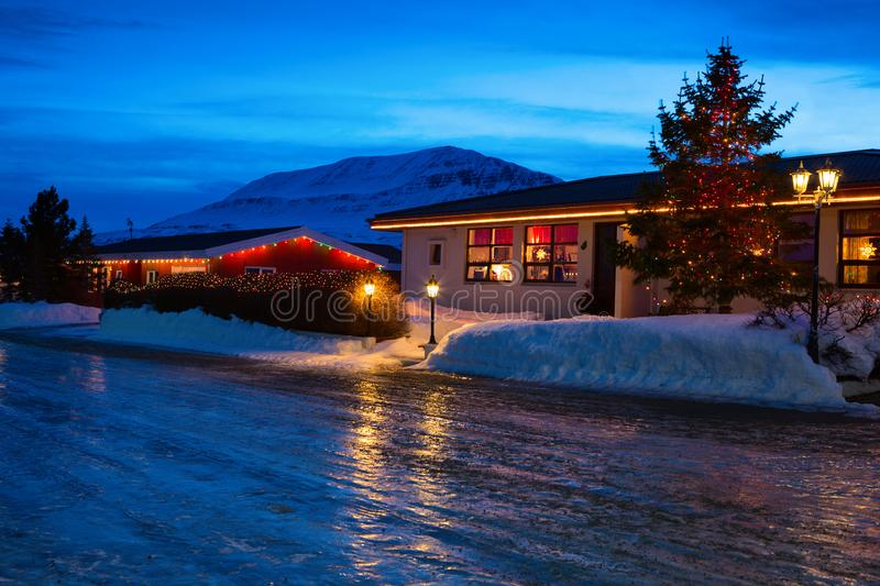 Typical Icelandic houses with Christmas decorations at the twilight near Akureyri, northern Iceland.  Slippery road in the foregro royalty free stock photography