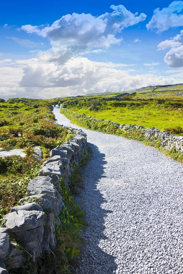 Typical Irish flat landscape in Aran Island with country road, stone walls and fields of grass for grazing animals Ireland - royalty free stock photography