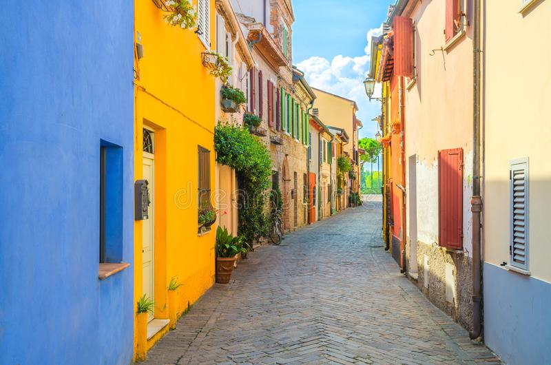 Typical italian cobblestone street with colorful multicolored buildings, traditional houses with green plants in Rimini royalty free stock image