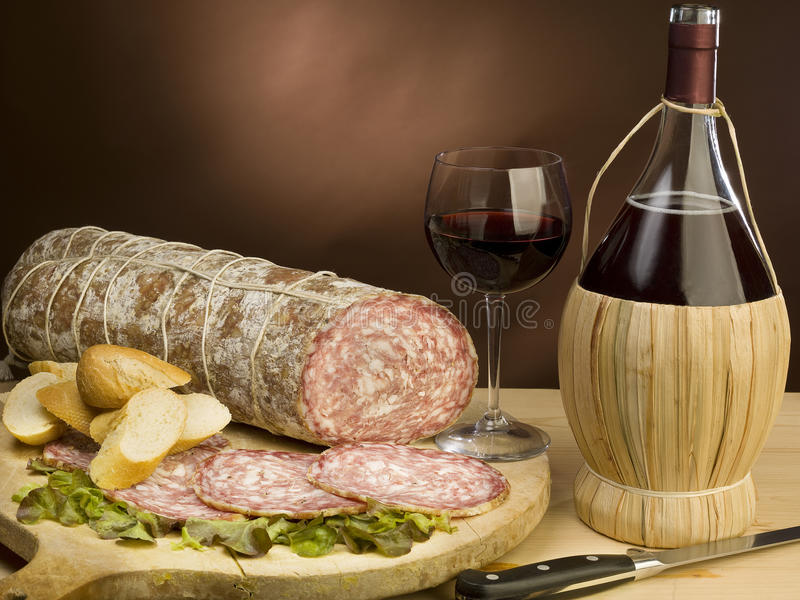 Typical Italian salami and red wine. Very good Italian salami, is waiting to be eaten with bread and red wine royalty free stock photography
