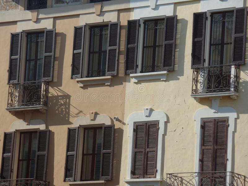 Typical Italian style building with brown shutters. Close up image of a typical Italian style building with brown shutters stock image