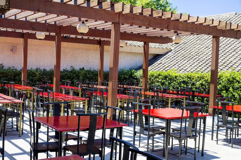 Typical little chinese restaurant with empty tables. Typical outdoor chinese restaurant with wooden red tables stock images