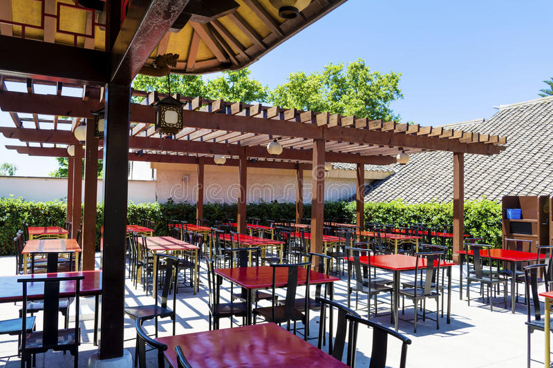 Typical little chinese restaurant with empty tables. Typical outdoor chinese restaurant with wooden red tables royalty free stock photos