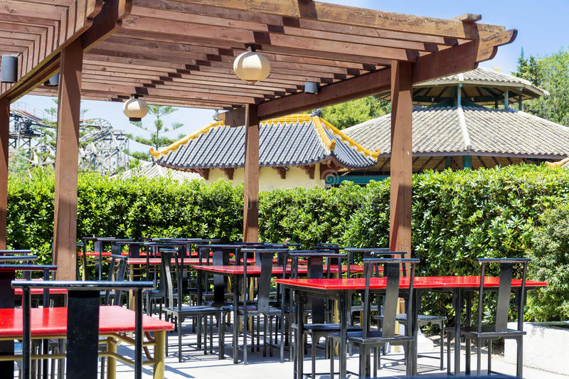Typical little chinese restaurant with empty tables. Typical outdoor chinese restaurant with wooden red tables stock photos