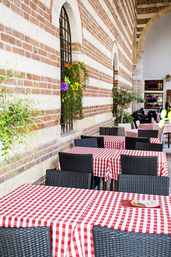 Typical little italian restaurant with empty tables. Typical little italian restaurant with wooden tables and red checkered tablecloths royalty free stock photo