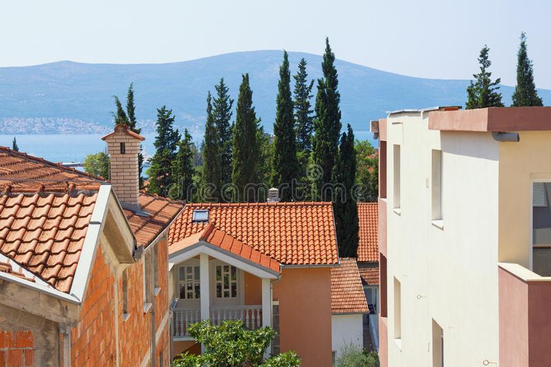 Typical Mediterranean urban landscape: houses with red tiled roof , green cypresses. Montenegro, Tivat town stock image