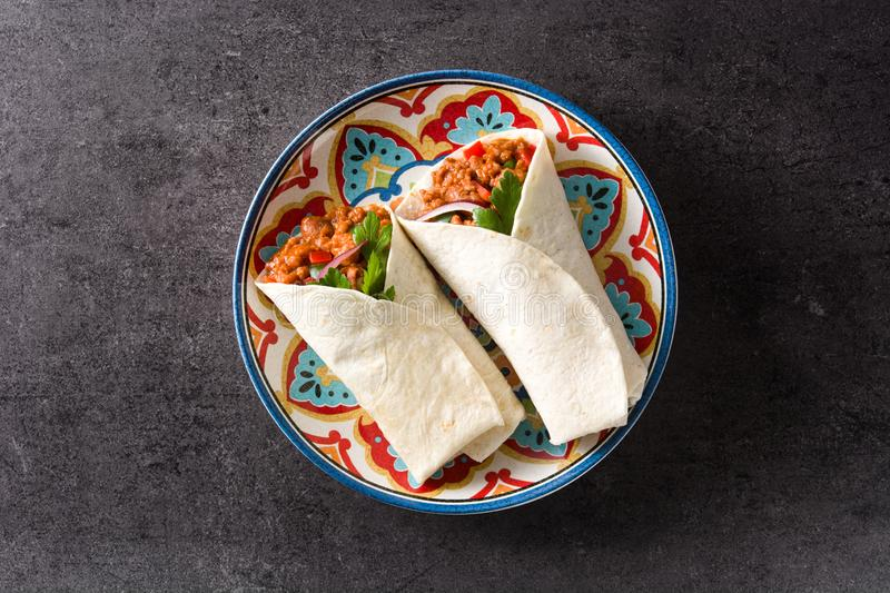 Typical Mexican burrito wrap with beef, frijoles and vegetables on black background. Top view royalty free stock images