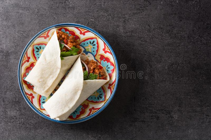 Typical Mexican burrito wrap with beef, frijoles and vegetables on black background. Top view. Copyspace stock photos