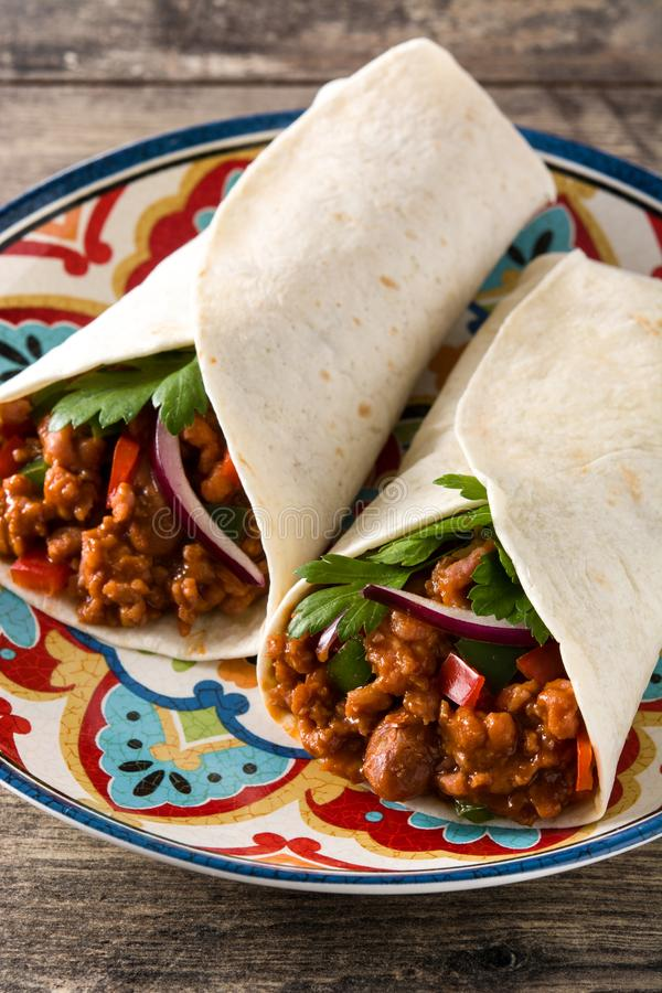 Typical Mexican burrito wrap with beef, frijoles and vegetables on wooden table. stock photography