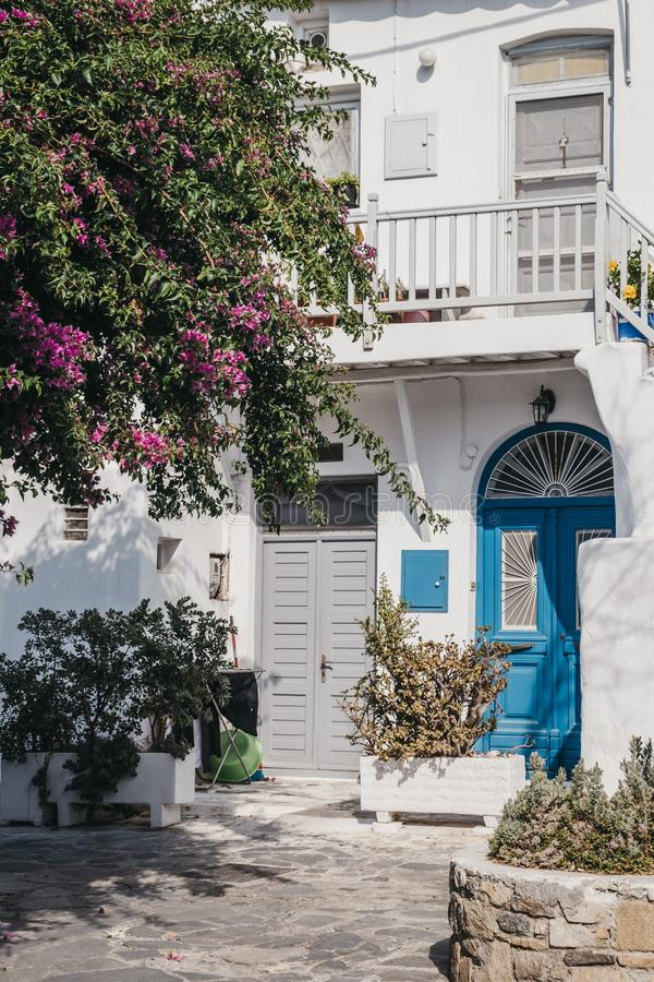 Typical Mykonian white house with blue front door pink blossoming tree in front, Mykonos, Greece. Facade of a typical Mykonian white house with blue front door stock photo