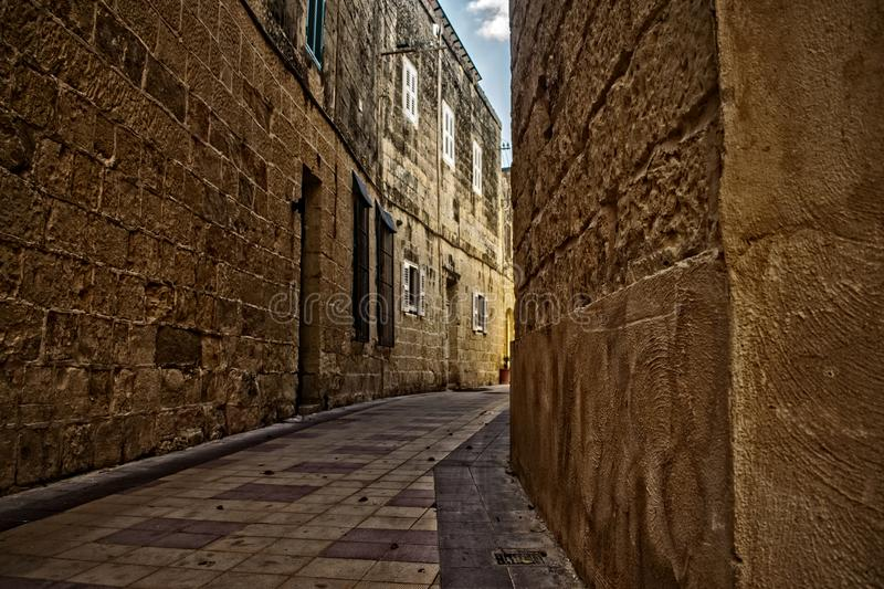 Narrow Road in the Old Town of Attard in Malta. A typical Narrow Road in the Old Town of Attard in Malta with limestone walls stock photo