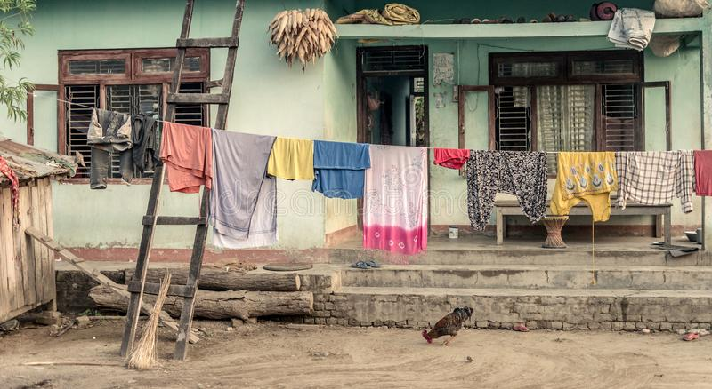 Typical nepalese yard in villlage. Typical old nepalese house with rope with washed clothes and on the yard in villlage close Chitwan royalty free stock image