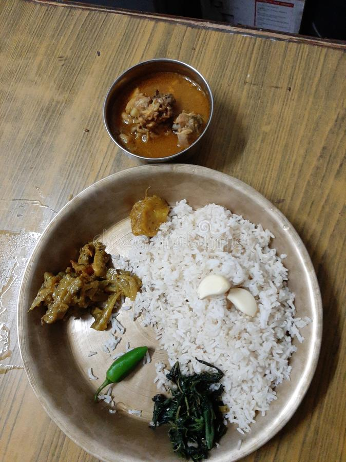 A typical nepali plate or thali in chures ko thal. Here it includes a bowl of meat , veg,  a chilli and two cloves of garlic. stock photo
