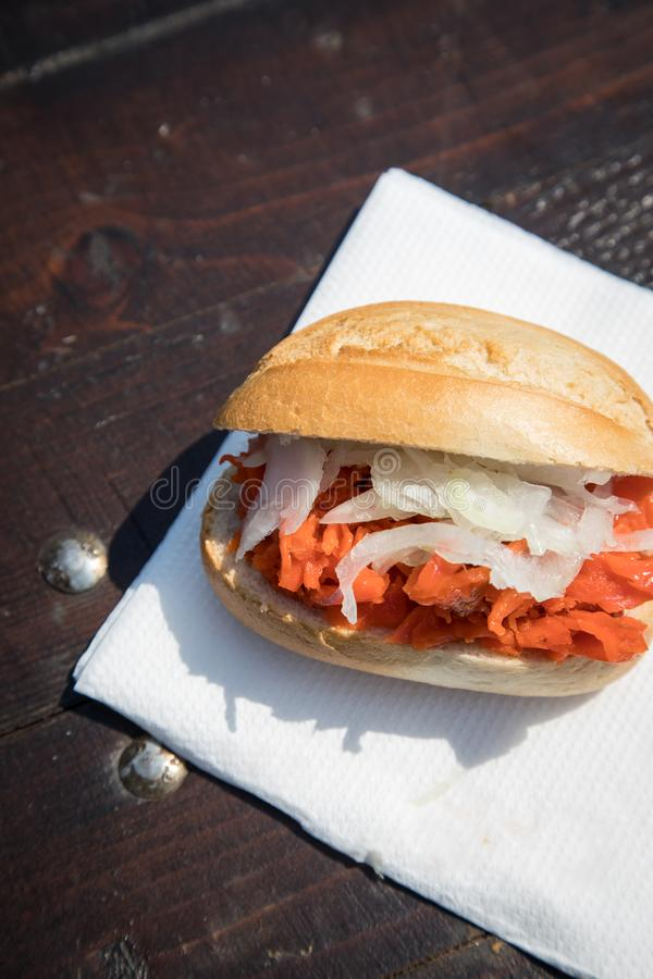 Typical North German Friesland cuisine is Alaska Pollack bun with onions on wooden table during fish market as fast regional snack stock photo