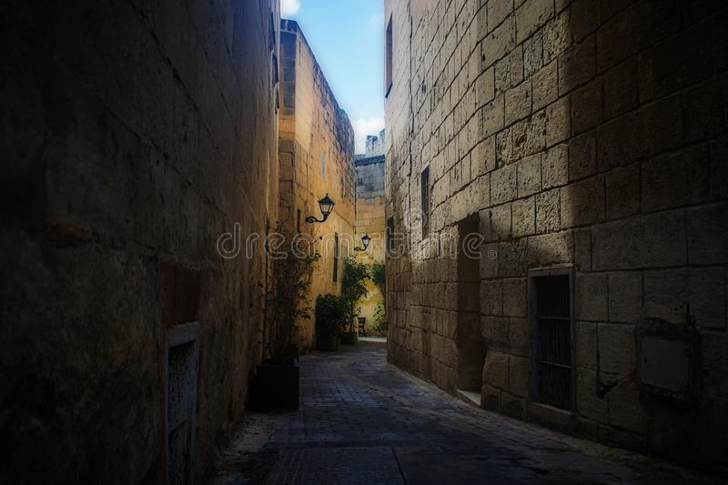 A Typical old Alleyway in Birkirkara, Malta. Featuring old houses, high stone walls and lanterns royalty free stock photo
