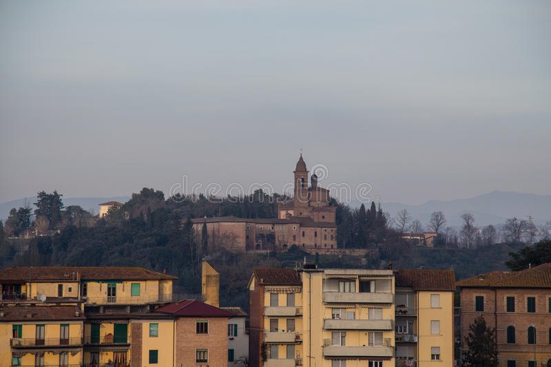 Typical old building in Siena and a church on background. Tuscany, Italy. royalty free stock images