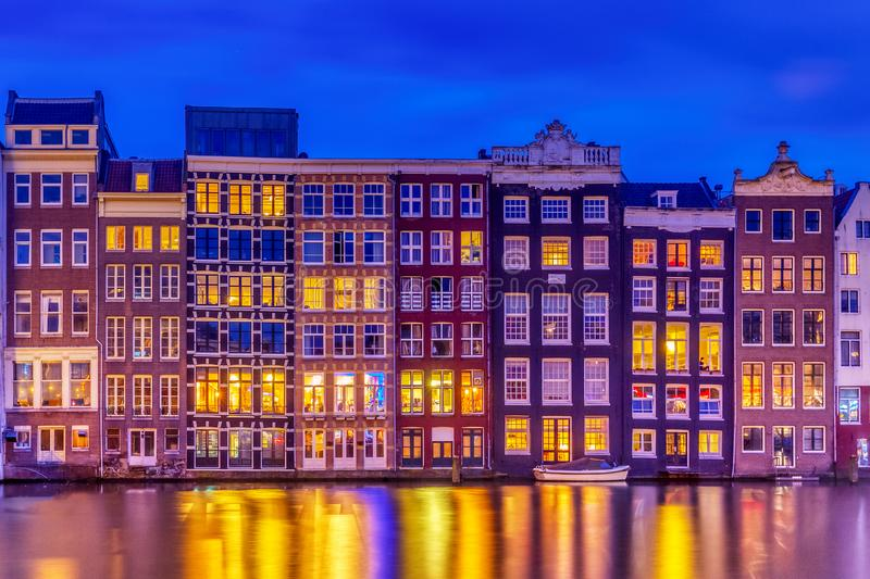 Typical old dutch houses over canal with reflections at twilight in Amsterdam, North Hilland, Netherlands. Amsterdam postcard stock photo