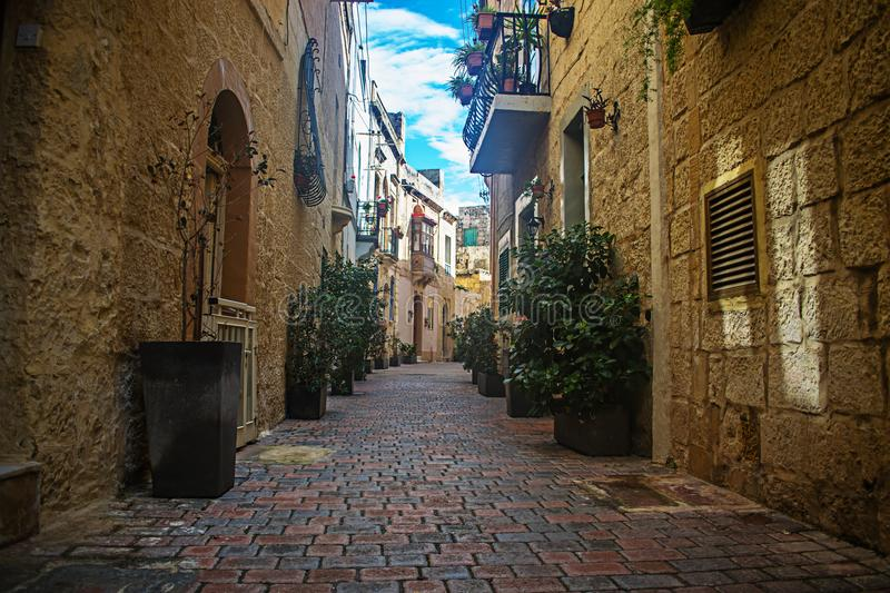 Old Streets and Houses in Birkirkara, Malta. A typical old narrow road in Birkirkara, Malta featuring old houses and high stone walls royalty free stock image