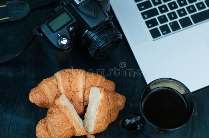 Typical photographer / blogger workplace in the morning. DSLR camera and laptop. Tasty croissants stock photo