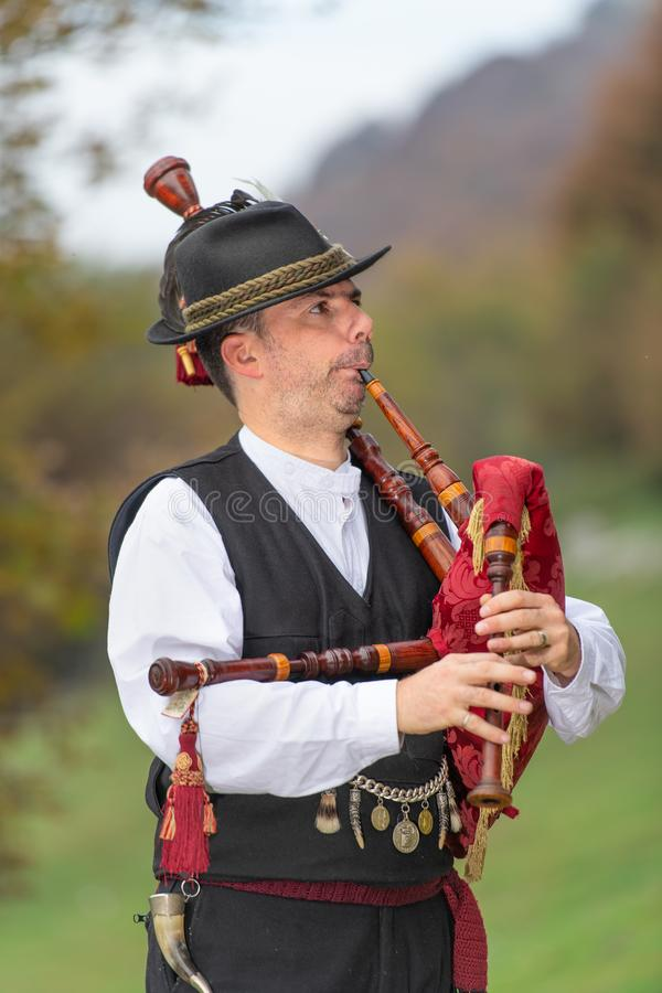 Typical player in traditional northern Italy bagpipe costume, an. Alpine valley of Bergamo stock photography
