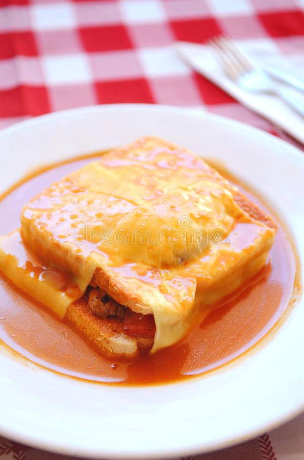 Typical Portugal food in Porto area: Francesinha. Francesinha is a Portuguese sandwich originally from Porto, made with bread, wet-cured ham, linguiça, fresh royalty free stock photo