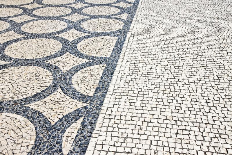 Typical portuguese floor made of small pieces of black and white. Stone in shape of circles and arcs Portugal - Europe stock photo