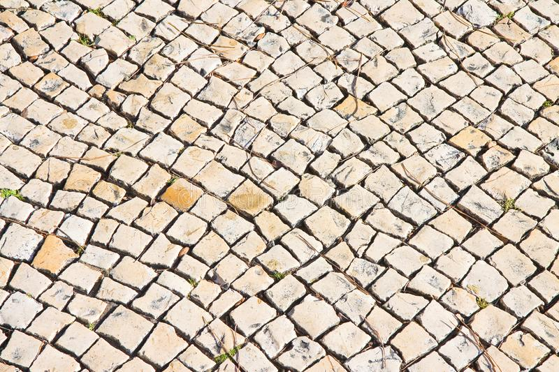 Typical Portuguese floor made of small pieces of bright stone.  royalty free stock image