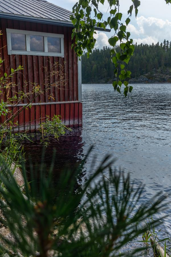 A typical red boat house on the shore of the Saimaa lake in Fin stock image
