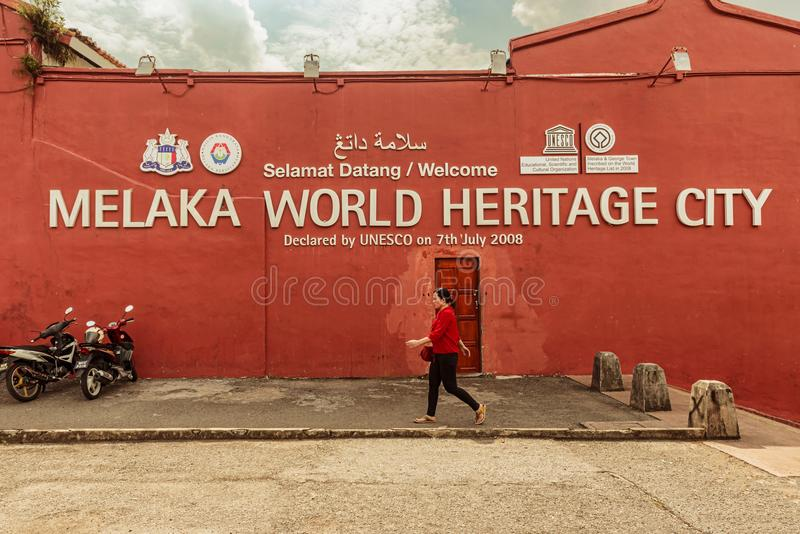 Typical red colonial building in the center of Melaka, Malaysia. Malacca, Melaka, Malaysia – Dec 15, 2017: Woman walking by the side wall of typical red royalty free stock image