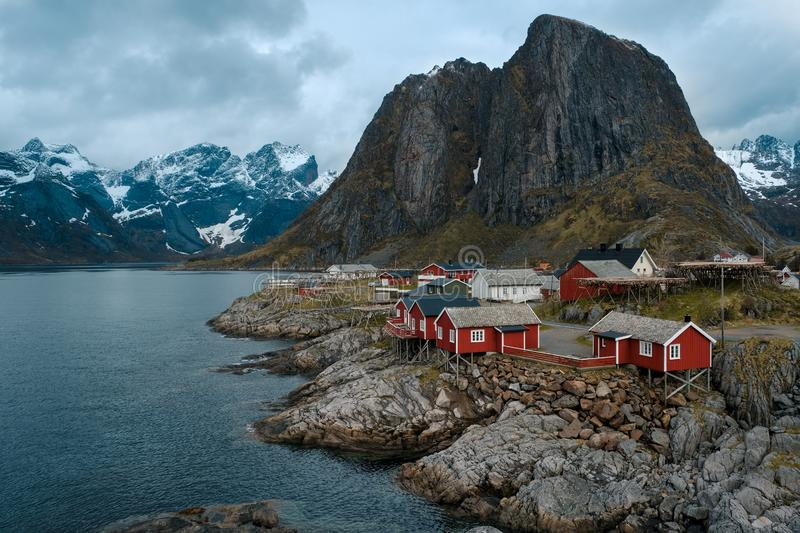 Typical red rorbu fishing huts with sod roof on Lofoten islands in Norway. Reflecting in fjord royalty free stock photography