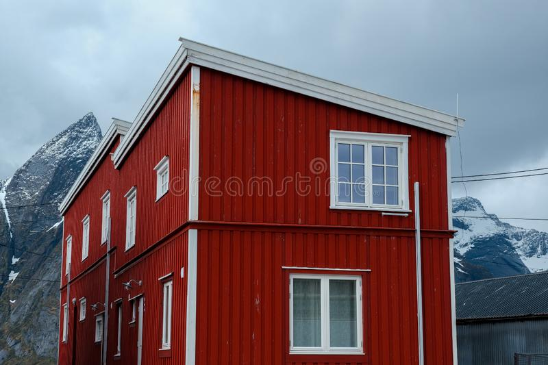 Typical red rorbu fishing huts with sod roof on Lofoten islands in Norway. Reflecting in fjord stock photo