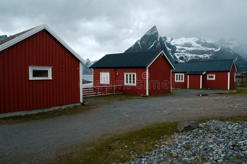 Typical red rorbu fishing huts with sod roof on Lofoten islands in Norway. Reflecting in fjord stock images