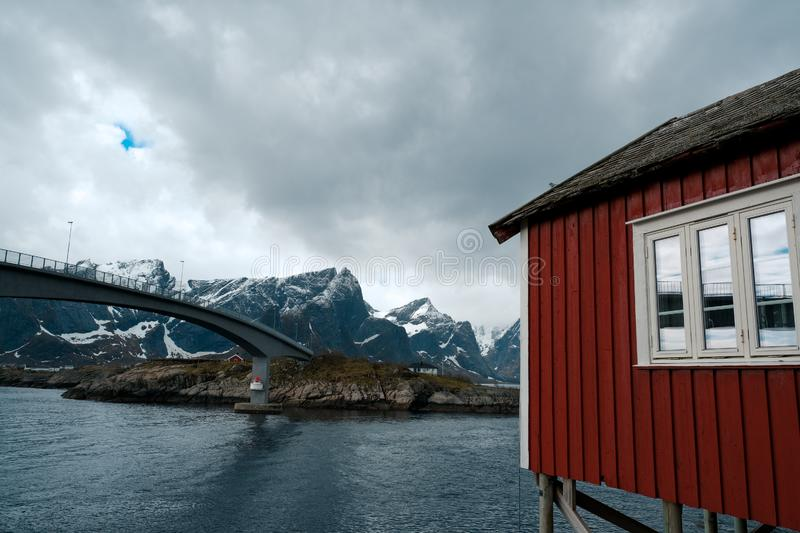 Typical red rorbu fishing huts with sod roof on Lofoten islands in Norway. Reflecting in fjord royalty free stock photos