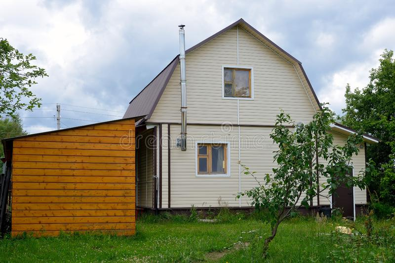 Typical Russian cottage, dacha in Russian. Dacha is a house for seasonal residence, located in the countryside. Designed for family recreation and the stock photo
