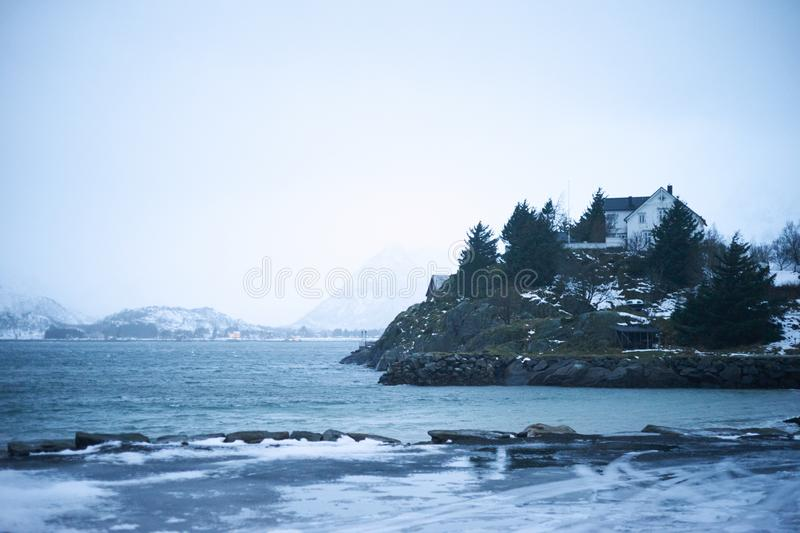Typical scandinavian house at fjord in front of snow covered mountains in winter royalty free stock images