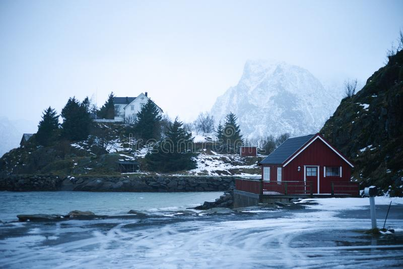 Typical scandinavian red house at fjord in front of snow covered mountains in winter stock photography
