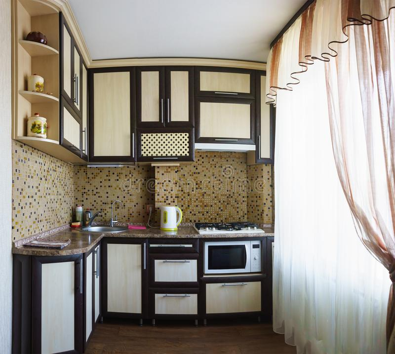 Typical small kitchen in an old standard house with a large bright window royalty free stock photography