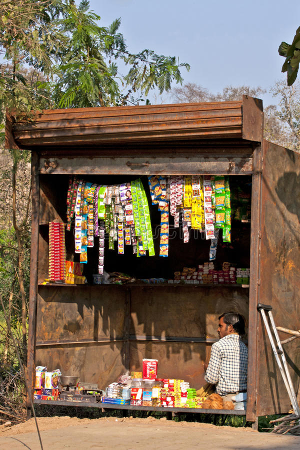 Typical small shop selling basic products in Indian villages. ORCHA, INDIA - CIRCA FEBRUARY 2011: Rusty garage-box like contraption is the shop where a man royalty free stock photography