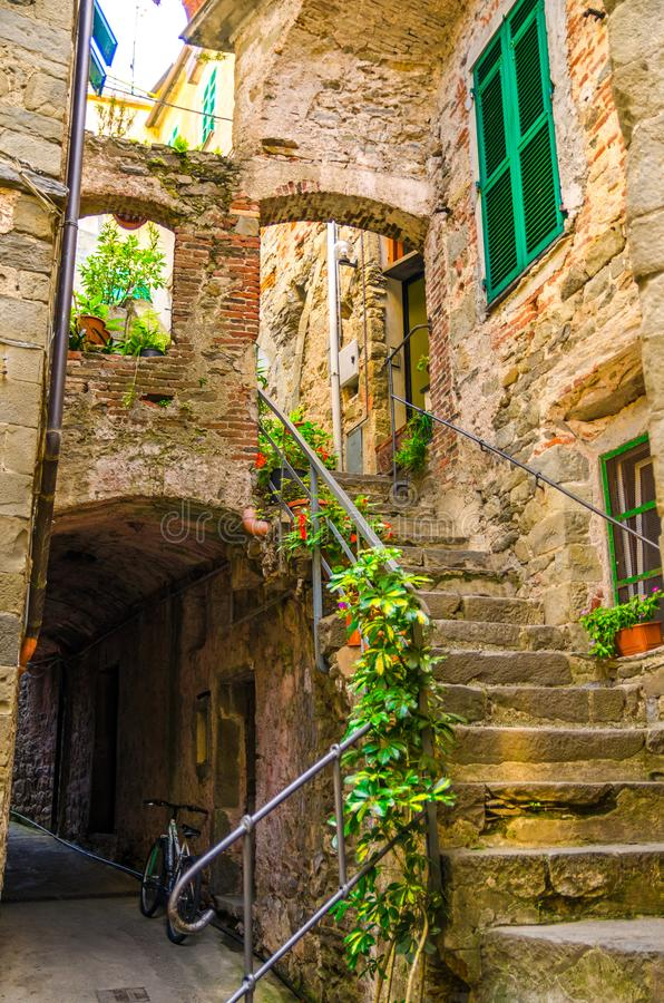 Typical small yard with stone buildings houses, stairs, shutter window and flower pots in Corniglia village, National park Cinque. Terre, La Spezia province stock photo