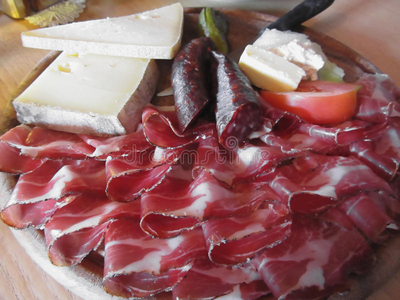 Typical South Tyrolean snack with speck, mountain cheese, smoked sausages and mountain butter stock photography