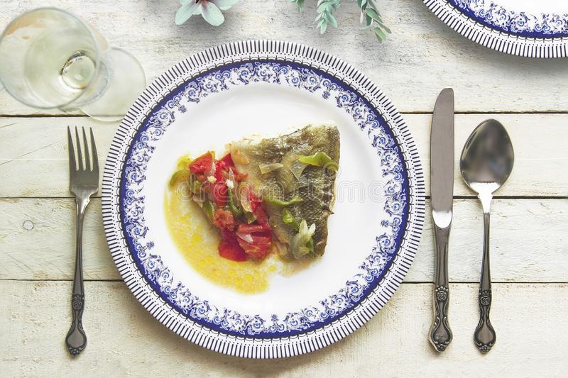 Typical Spanish and Andalusian Cod with Samfaina served on a rustic wooden table next to somw white wine and floral decoration stock photography
