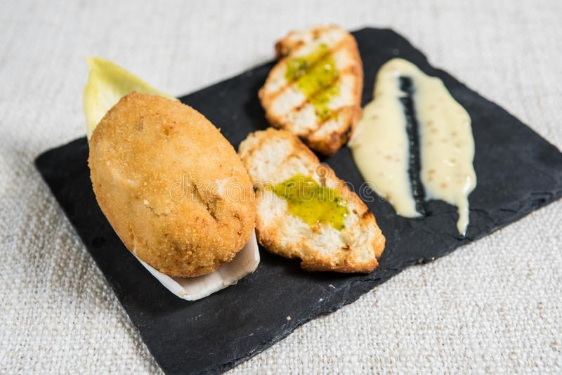 Typical spanish croquette cooked with bread and sauce on slate plate. Close up royalty free stock photos