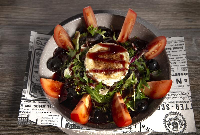 Typical Spanish goat cheese salad on wooden background. Isolated image stock photo